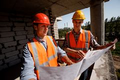 Architect and structural engineer dressed in shirts, orange work vests and helmets explore construction documentation on royalty free stock images
