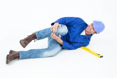 Architect suffering from knee pain after falling. Full length of architect suffering from knee pain after falling against white background Stock Image