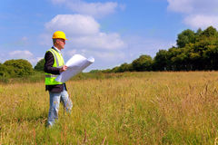 Architect surveying a new building plot. Architect wearing site safety gear and holding plans surveying a new building plot stock image