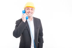 Architect talking on blue big telephone receiver. Portrait of architect talking on blue big telephone receiver wearing yellow hardhat and smiling isolated on Royalty Free Stock Photography