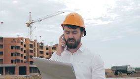 Architect talking on cell phone on a construction site. stock video footage