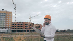 Architect talking on cell phone on a construction site. stock footage