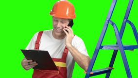 Architect talking on cell phone, green screen. Cheerful foreman talking on mobile phone while looking at clipboard, chroma key background stock footage