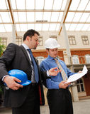 Architect talking to investor over the blueprints. Two architects reviewing the blueprints royalty free stock photo