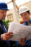 Architect talking to investor over the blueprints. Two architects reviewing the blueprints royalty free stock photography