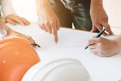 Architect Team Brainstorming Planning Design, Civil engineer sketching a blueprint of construction project with small house model. And safety helmet in office stock photos