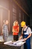 Architect team checking blueprint on work site Stock Image