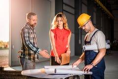 Architect team checking blueprint on work site Stock Photo