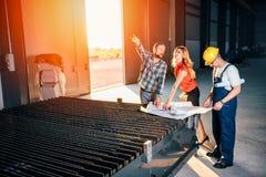 Architect team checking blueprint on work site Royalty Free Stock Photo