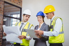 Architect team discussing while holding blueprint and clipboard Royalty Free Stock Images
