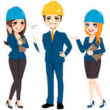 Architect Team Group. Standing wearing safety helmet hat and holding blueprints Royalty Free Stock Images