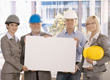 Architect team holding poster in office. Architect team in hardhat holding blank poster for copyspace in office, smiling Stock Photos