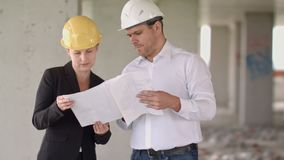 Architect team man and woman discussing about building plan for construction at job site stock footage