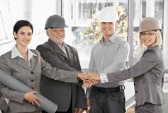 Architect team in office holding hands in unity. Expressing teamwork, wearing hardhat, smiling at camera Royalty Free Stock Images