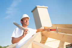 Architect on top of a brand new house. Young architect with blueprint on the top of a house that is currently under construction Royalty Free Stock Photography