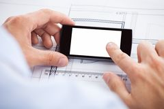 Architect touching smartphones screen over bluepri Royalty Free Stock Photo