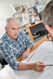 Architect trying to convince client. Architect stock image