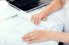 Architect is unwrapping project. Architect is unwrapping her project Royalty Free Stock Image