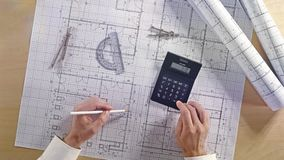 Architect using calculator on architectural blueprint house building plan with pencil, ruler, compasses and square flatlay - 4K UH stock footage