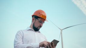 Architect using digital tablet agriculture windmill technology supervisor protective uniform renewable energy windpower. Sustainability engineering development stock video