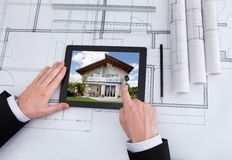 Architect using digital tablet on blueprint in office Royalty Free Stock Photos