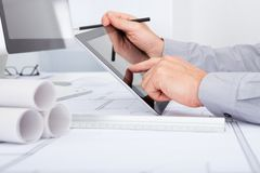 Architect using digital tablet. Close-up Of Architect Using Digital Tablet Over Blue Print Royalty Free Stock Images