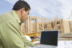 Architect Using Laptop At Site. Architect using laptop at construction site Royalty Free Stock Photography