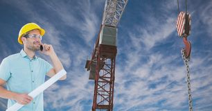 Architect using mobile phone while holding blue print by crane against sky Stock Image