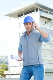 Architect using mobile phone outside building Stock Photo