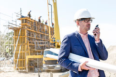 Architect using walkie-talkie while holding blueprints at construction site Stock Image