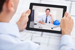 Architect video conferencing with colleague. Cropped image of male architect video conferencing with colleague through digital tablet in office royalty free stock images