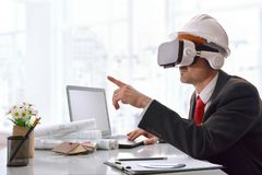 Architect visualizing 3d content in virtual reality glasses in o. Architect visualizing 3d content in virtual reality glasses in the office. Horizontal Stock Images