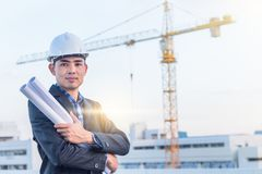 The architect wear white safety helmet and hold the blueprint wi. royalty free stock image