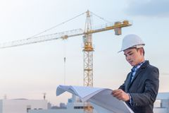 The architect wear white safety helmet and verify the blueprint Stock Photos