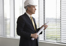 An architect wearing a hard hat holding plans Royalty Free Stock Images