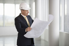 An architect wearing a hard hat holding plans Stock Photo