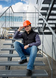 Architect wearing hard hat sitting on metal staircase at factory Royalty Free Stock Photos