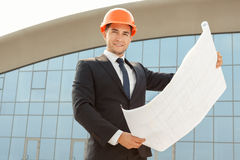 Architect wearing hardhat inspecting blueprints Royalty Free Stock Image