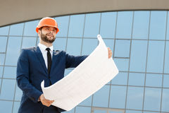 Architect wearing hardhat inspecting blueprints Royalty Free Stock Photos