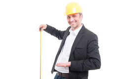 Architect wearing hardhat showing measuring tape. Isolated on white background Stock Photos