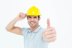 Architect wearing hardhat while showing thumbs up sign. Portrait of architect wearing hardhat while showing thumbs up sign over white background Royalty Free Stock Image