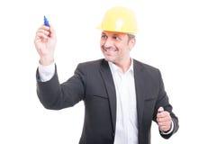 Architect wearing hardhat writing with marker. And smiling isolated on white background Royalty Free Stock Image