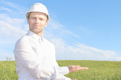 Architect in white helmet is holding his hands. Young beauty arc. Hitect offers engineering services. Concept of workers or architecture. Reliable partner in Royalty Free Stock Image