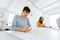 Architect woman with blueprint writing at office Stock Photography