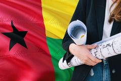 Architect woman holding blueprint against Guinea Bissau waving flag background. Construction and architecture concept.  royalty free stock photo