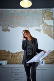 Architect woman talking phone holding plan paper Royalty Free Stock Photos