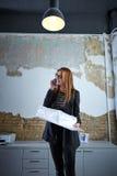 Architect woman talking phone holding plan paper Stock Photo
