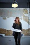 Architect woman talking phone holding plan paper Royalty Free Stock Photo