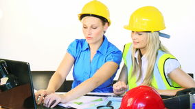 Architect women working together in office. Attractive young blonde architect women working together with a laptop and plans in office in High Definition stock video footage