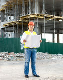 Architect at work reading blueprints on building site Stock Image